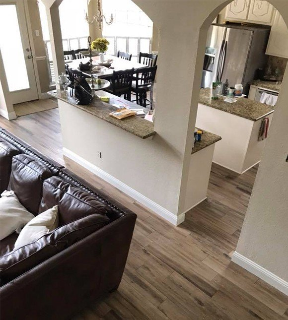 Laminate flooring in open floor plan living dining kitchen space