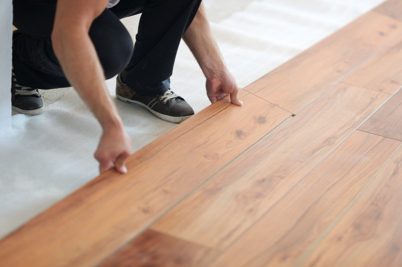 a contractor laying wood flooring in a person's home