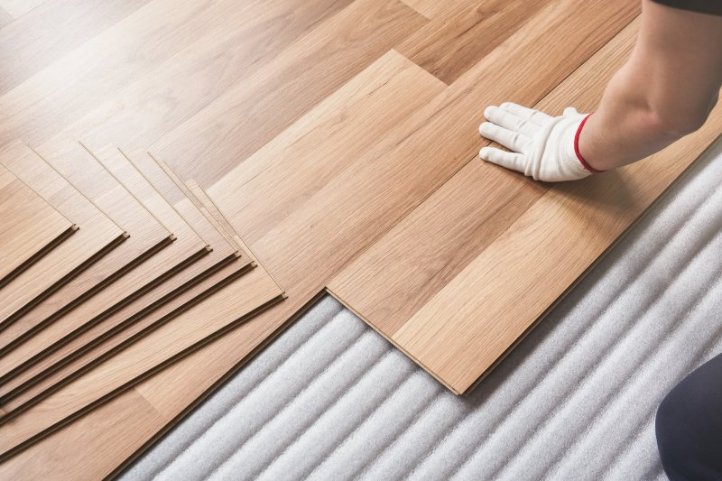 a professional laying laminate flooring in a person's home