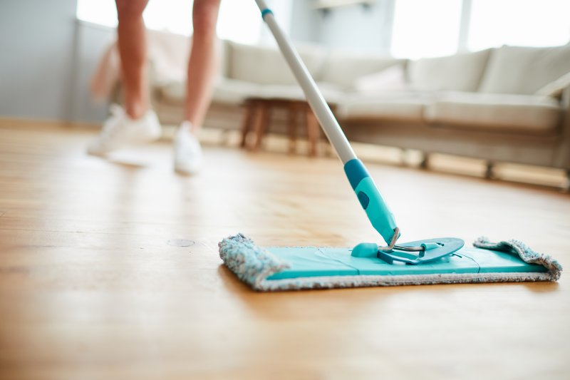an up-close image of a person cleaning their floors with a modern mop