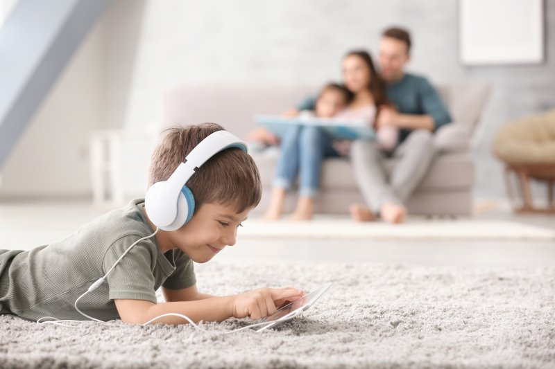 a little boy wearing headphone and playing on a tablet while lying on the carpet