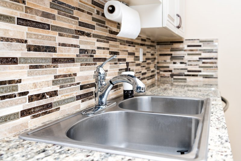 an up-close look of a kitchen sink, complete with a detailed backsplash