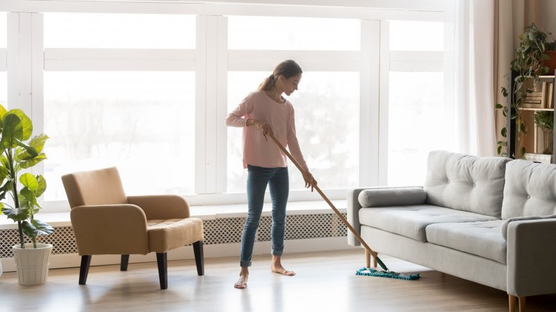 a woman using a dust mop to clean her floors