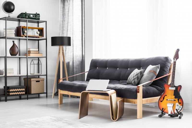 a room with a couch, decorative shelving, guitar stand, and small table