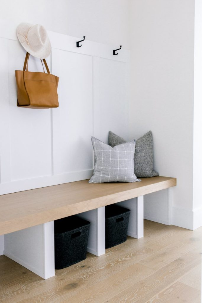 a bare mudroom with only a few pillows and a purse and hat